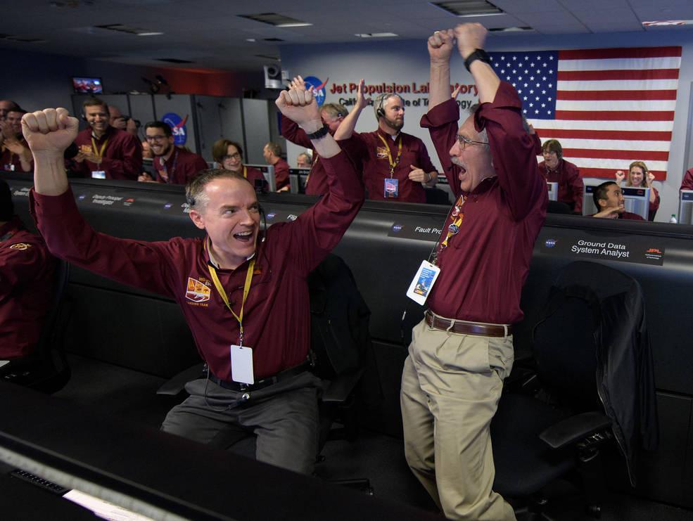 I membri del team Mars InSight Kris Bruvold, a sinistra, e Sandy Krasner reagiscono dopo aver ricevuto conferma che InSight è atterrato