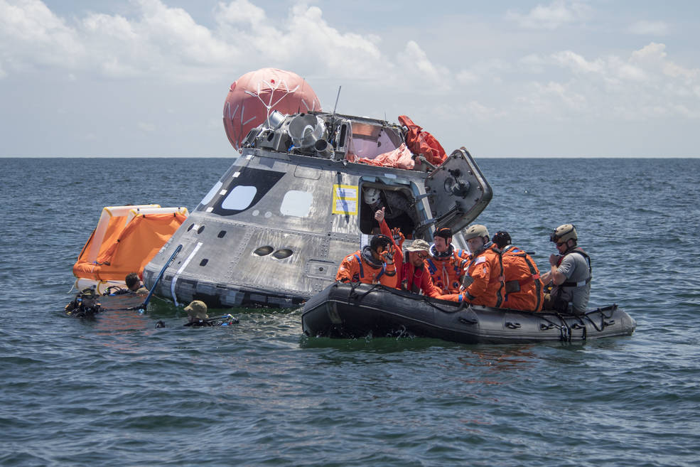 Orion capsule floats in sea with crew in orange flight suits in raft nearby