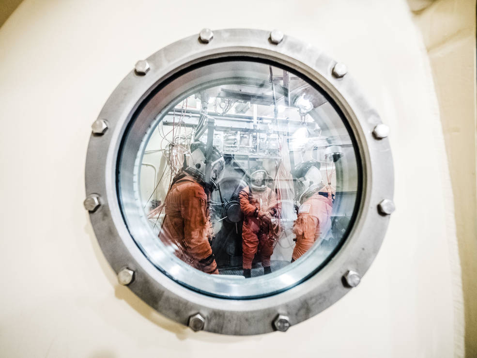 Technicians in pressure suits viewed through round window