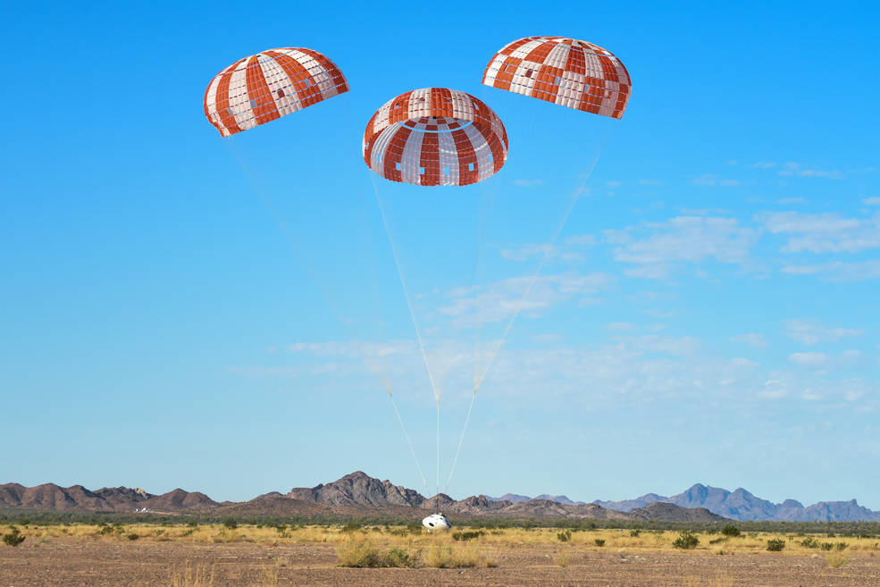 Orion spacecraft with parachutes deployed descends to Earth