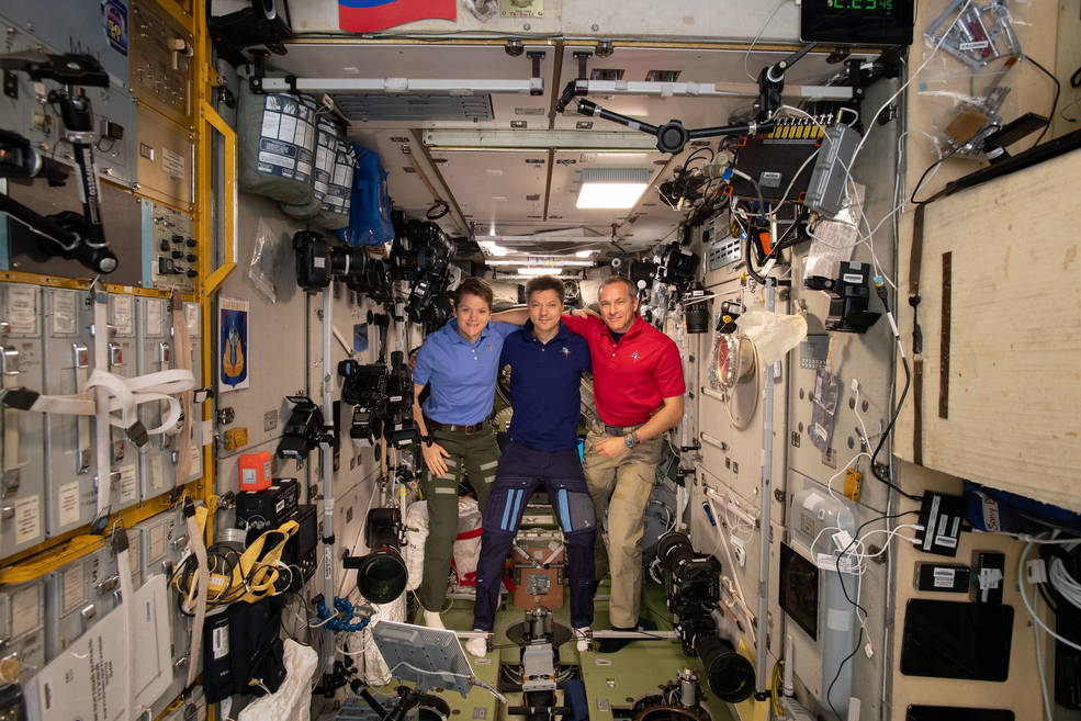 Expedition 58/59 crew members gather inside the Zvezda service module for a crew portrait.