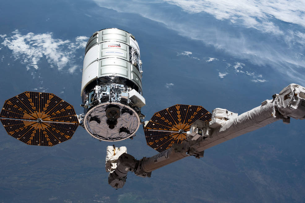 The U.S. Cygnus space freighter is pictured as the Canadarm2 robotic arm
