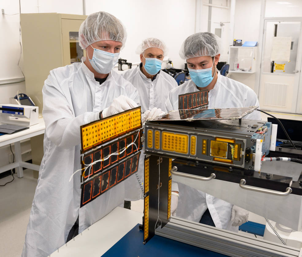 Researchers perform a solar array deployment and gimbal motion test on the spacecraft in a clean room.
