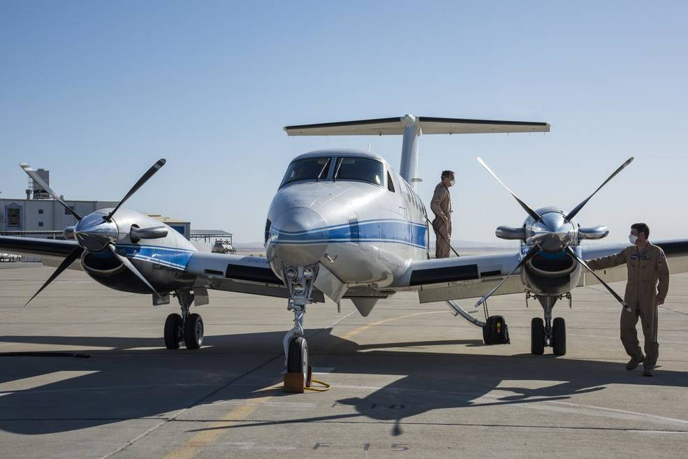 """A flight crew prepares for the B200 King Air Sub-Mesoscale Ocean Dynamics Experiment (S-MODE) at NASA's Armstrong Flight Research Center in Edwards, California. From left to right are Jeroen Molemaker and Scott """"Jelly"""" Howe."""
