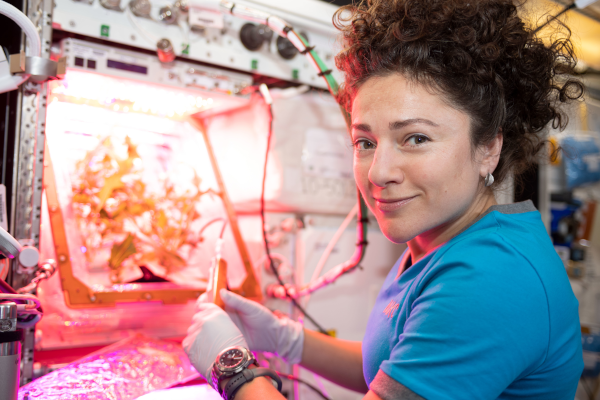 astronaut Jessica Meir tending to plants inside the space station