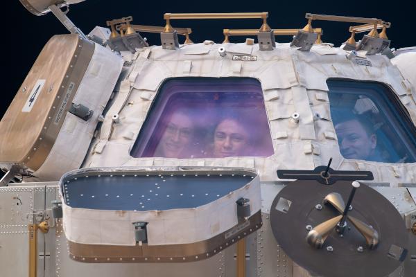astronauts christina koch, jessica meir, and andrew morgan seen through the cupola window
