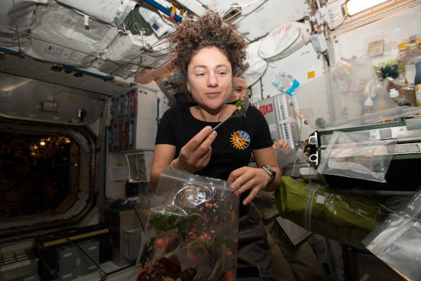 astronaut Jessica Meir eating leafy greens inside the space station