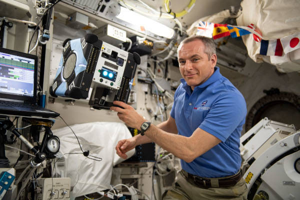 astronaut David Saint-Jacques working with the astrobee robot inside the space station