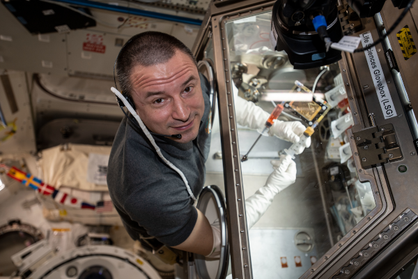 astronaut andrew morgan using the glovebox inside the space station