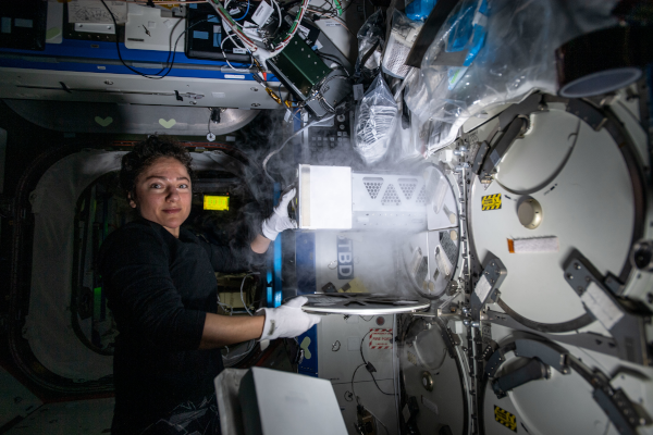 astronaut jessica meir working with cold stowage inside the space station