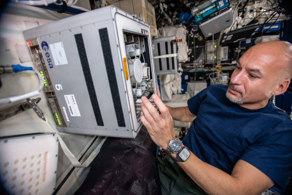astronaut Luca Parmitano installing hardware inside the space station