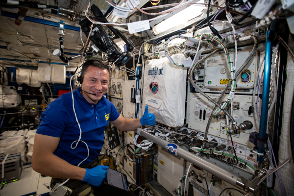 astronaut andrew morgan setting up equipment inside the space station