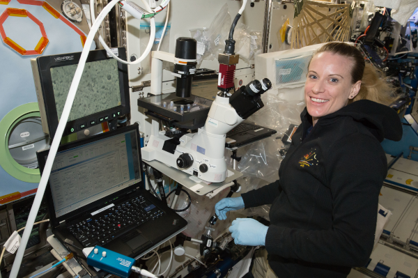 Η Kate Rubins σταματάει για μια φωτογραφία ενώ χρησιμοποιεί το μικροσκόπιο για να διεξάγει τις πειραματικές λειτουργίες των καρδιακών κυττάρων