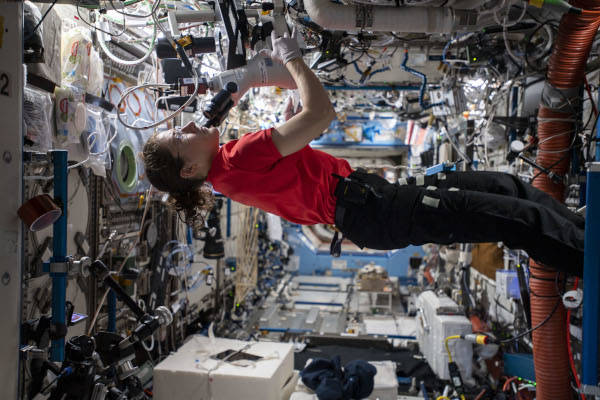 astronaut Christina Koch using a microscope inside the space station