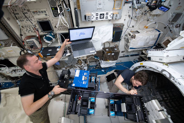 astronauts Nick Hague and Anne McClain prepping hardware to be moved outside the space station