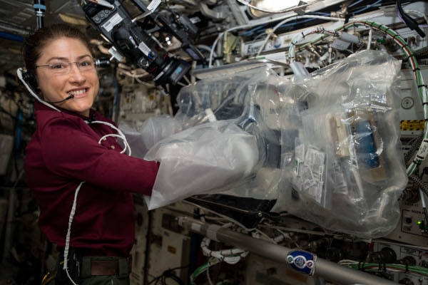 astronaut Christina Koch using bioprinting hardware inside the space station