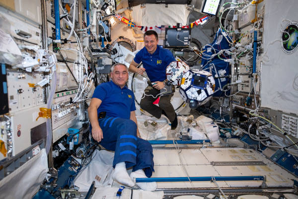 cosmonaut Alexander Skvortsov and astronaut Andrew Morgan floating next to SPHERES robots inside the space station