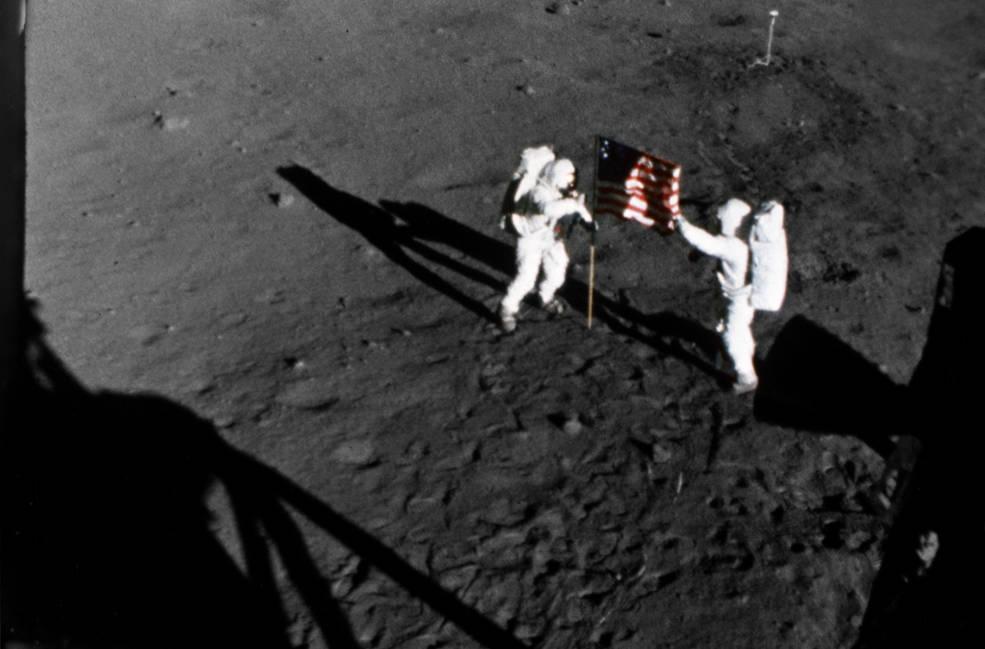"""รูปต่อไปนี้คือ 1 ในรูปของม้วนฟิล์มที่ได้เคยถูกบันทึกเอาไว้เมื่อวันที่ 20 กรกฎาคม ปี ค.ศ. 1969 ที่แสดงให้เห็น ขณะที่นักบินอวกาศจากภารกิจอะพอลโล่ 11 กำลังปักเสาธงชาติอเมริกาลงสู่พื้นผิวของดวงจันทร์ โดยนักบินอวกาศทั้งสองคนในรูปนี้ประกอบไปด้วย 'นีล อาร์มสตรอง' (Neil A. Armstrong) ที่ยืนอยู่ทางซ้ายมือขณะกำลังปกธงลงบนพื้น และ 'บัซซ์ อัลดริน' (Edwin E. """"Buzz"""" Aldrin Jr.) ที่คอยช่วยประคองเสาธงอย่างระมัดระวังทางขวาของภาพ ซึ่งรูปนี้ถูกถ่ายเอาไว้โดยกล้องฟิล์มขนาด 16 มม. ที่ถูกติดตั้งไว้อยู่บนยานลงดวงจันทร์ (Lunar Module) ของพวกเขา (ภาพจาก NASA)"""