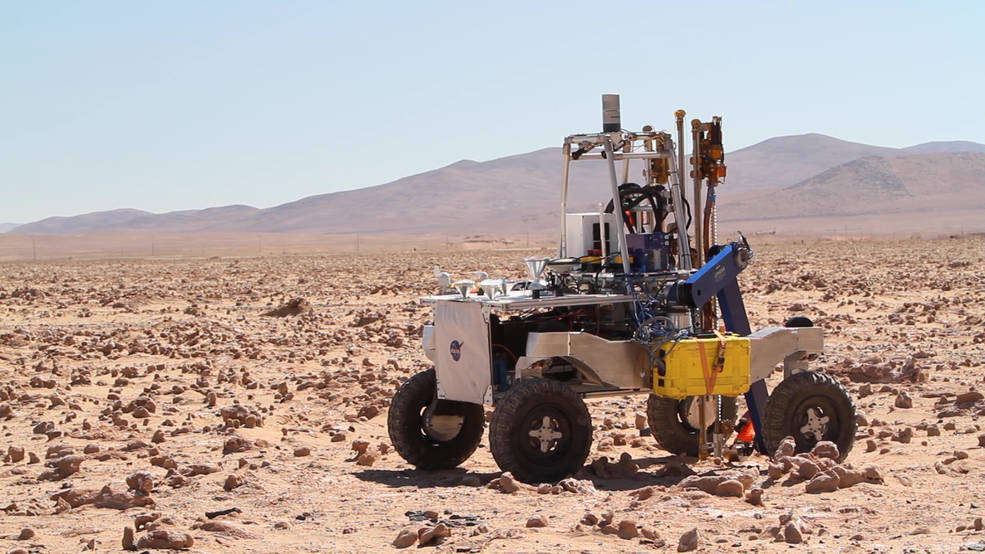 A four-wheeled rover in a dramatic desert landscape with instrumentation and a drill mounted on top of it.