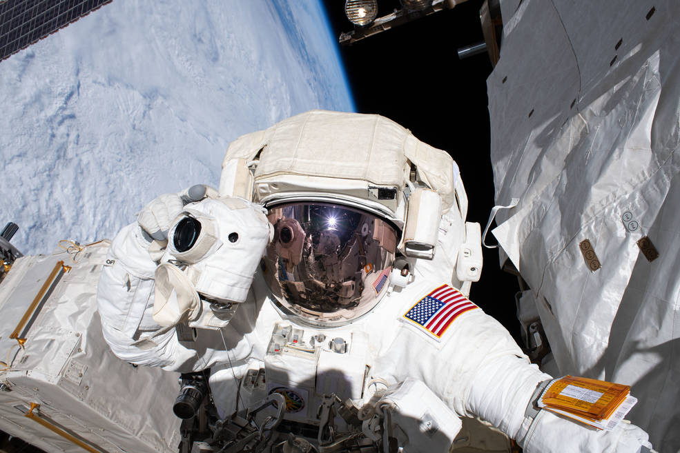 NASA astronaut Andrew Morgan prepares to take a photograph while conducting a spacewalk outside the International Space Station