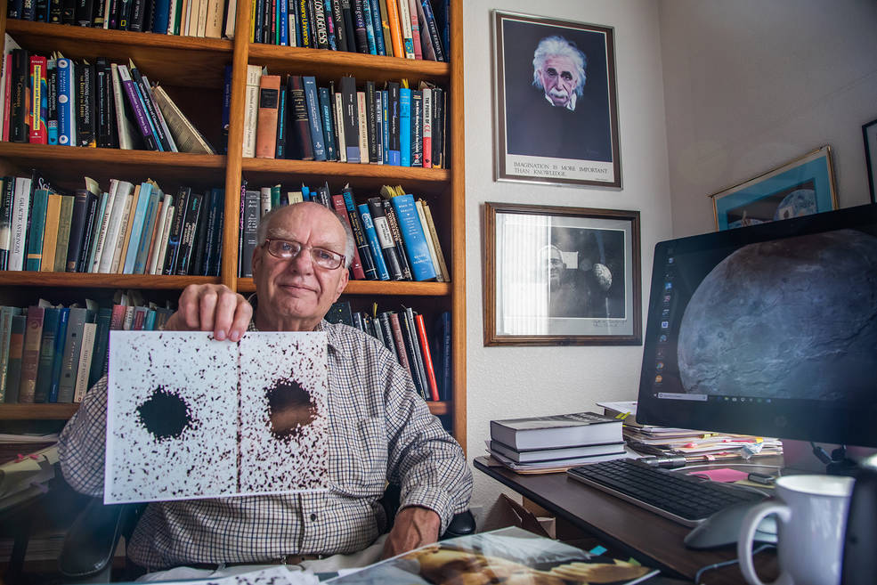 40 years after his important discovery, Jim Christy holds two of the telescope images he used to spot Pluto's large moon Charon