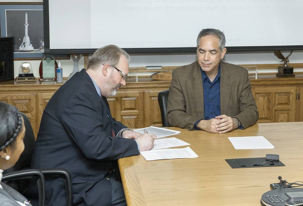 Kraettli Epperson and David McBride sign an agreement to commercialize aircraft tracking system for unmanned aircraft.