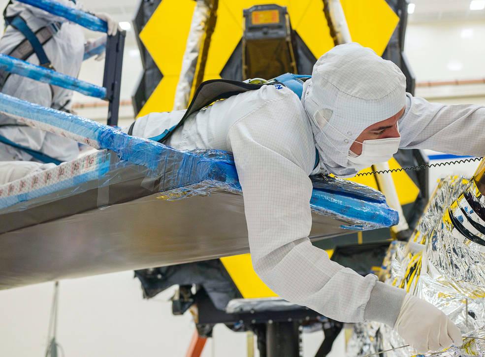Ein Techniker arbeitet sorgfältig daran, den Sonnenschutz des James Webb-Weltraumteleskops zu falten.