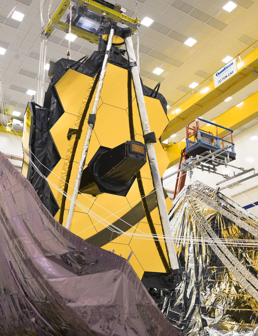 The Webb Telescope's sunshield is lifted vertically on both sides in preparation for the folding process.