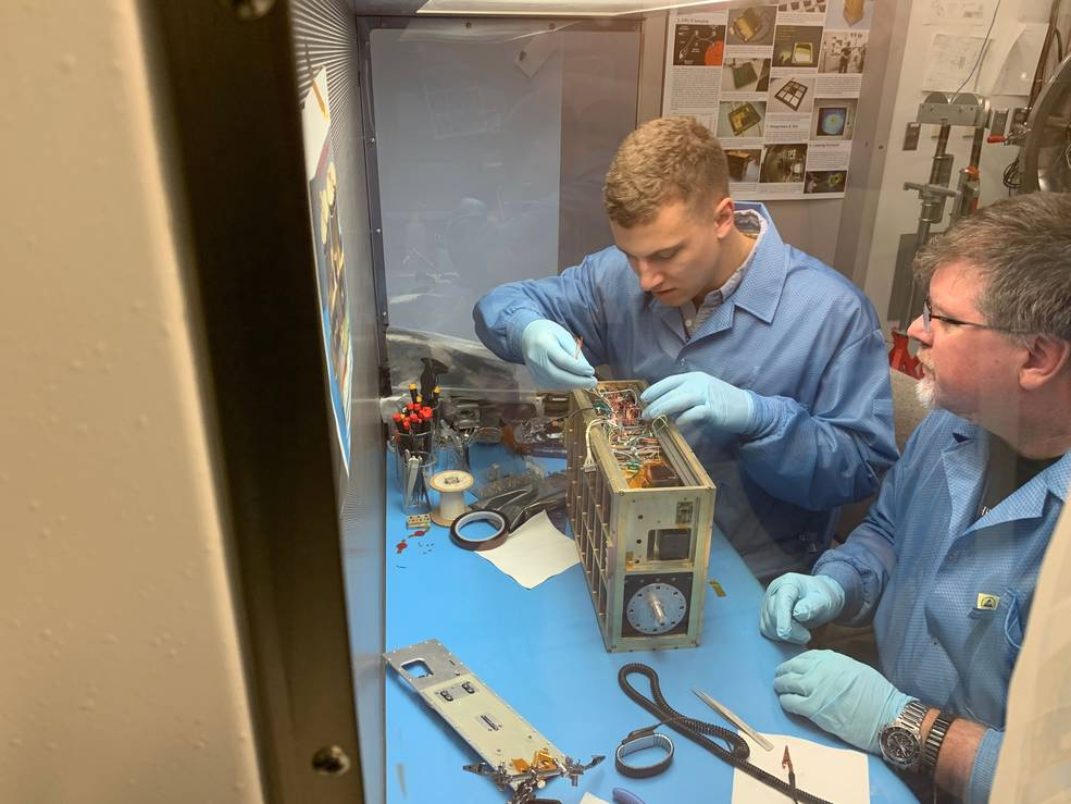 Two people work on a small satellite