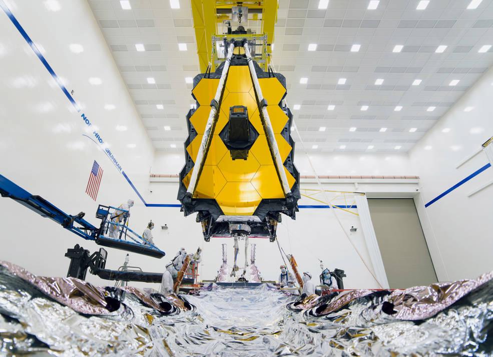 As equipes de integração orientam cuidadosamente a seção do telescópio suspenso da Webb no lugar acima do seu Elemento Espacial.