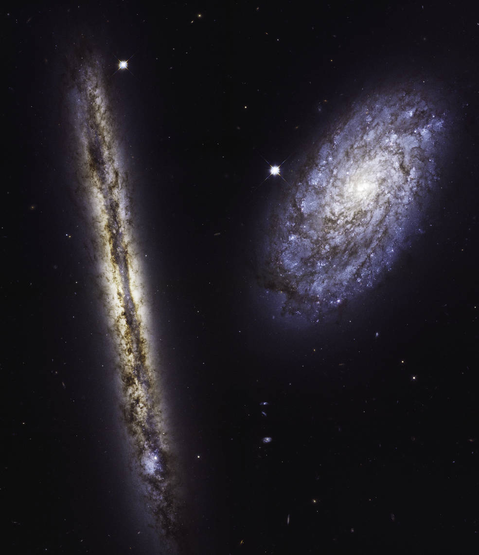 two spiral galaxies, one edge on, one facing us