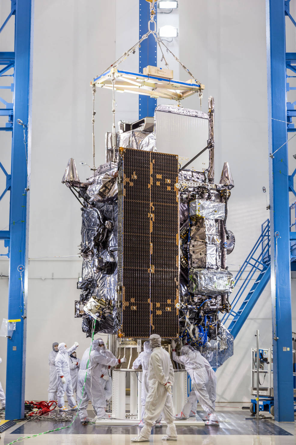 men in paper suits surround satellite in cleanroom