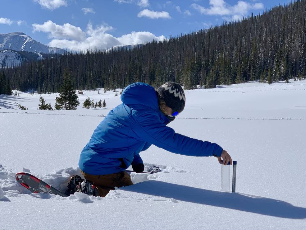 Lucas kneeling in snow with measuring equipment, select to view full image