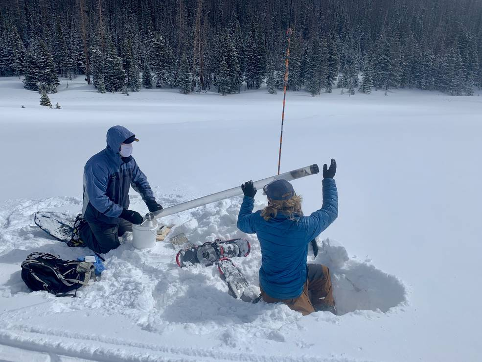 Two graduate students in parkas and snowshoes collect a snow-water equivalent core sample at a snowy site in Colorado, select to view full image