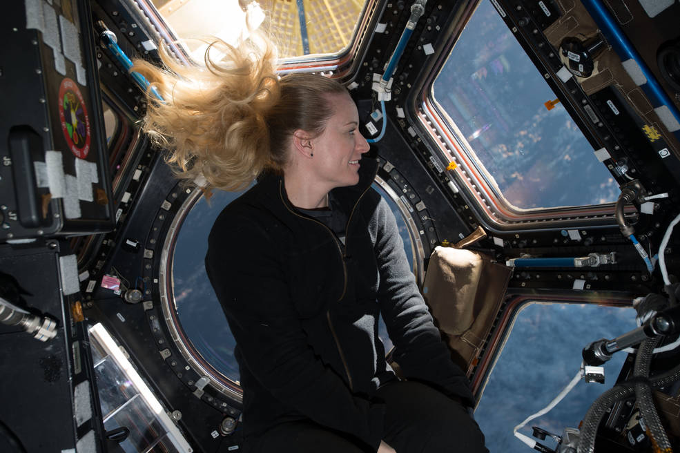 NASA astronaut Kate Rubins in front of the windows in the International Space Station's cupola module in 2016