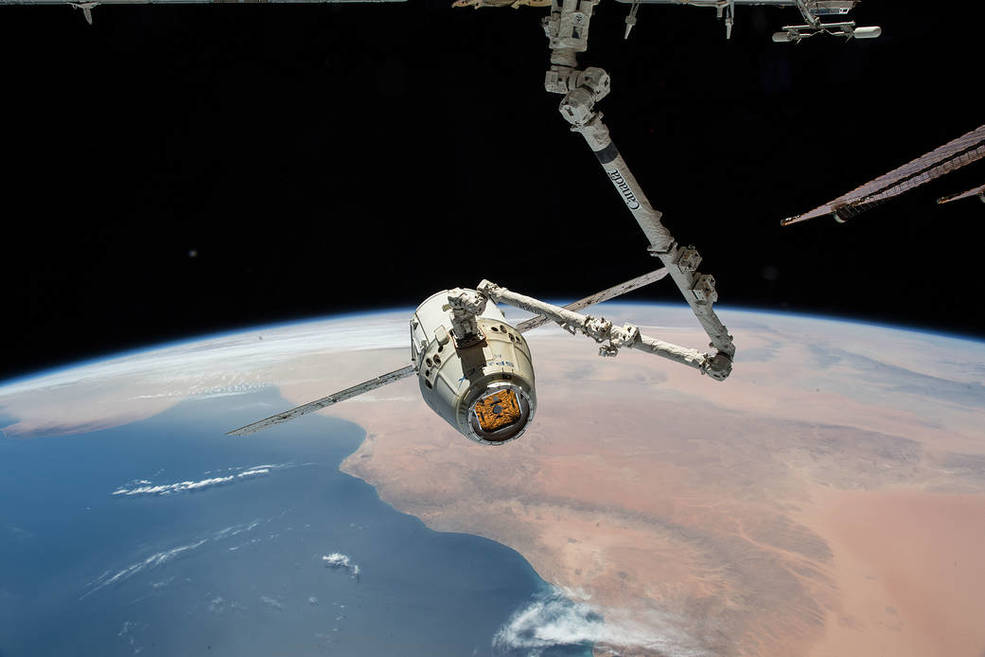 The SpaceX Dragon cargo craft is pictured in the grips of the Canadarm2 robotic arm of the International Space Station