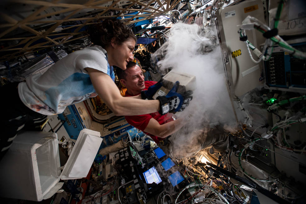 NASA astronauts Christina Koch and Andrew Morgan stow biological research samples into a science freezer located inside the ISS