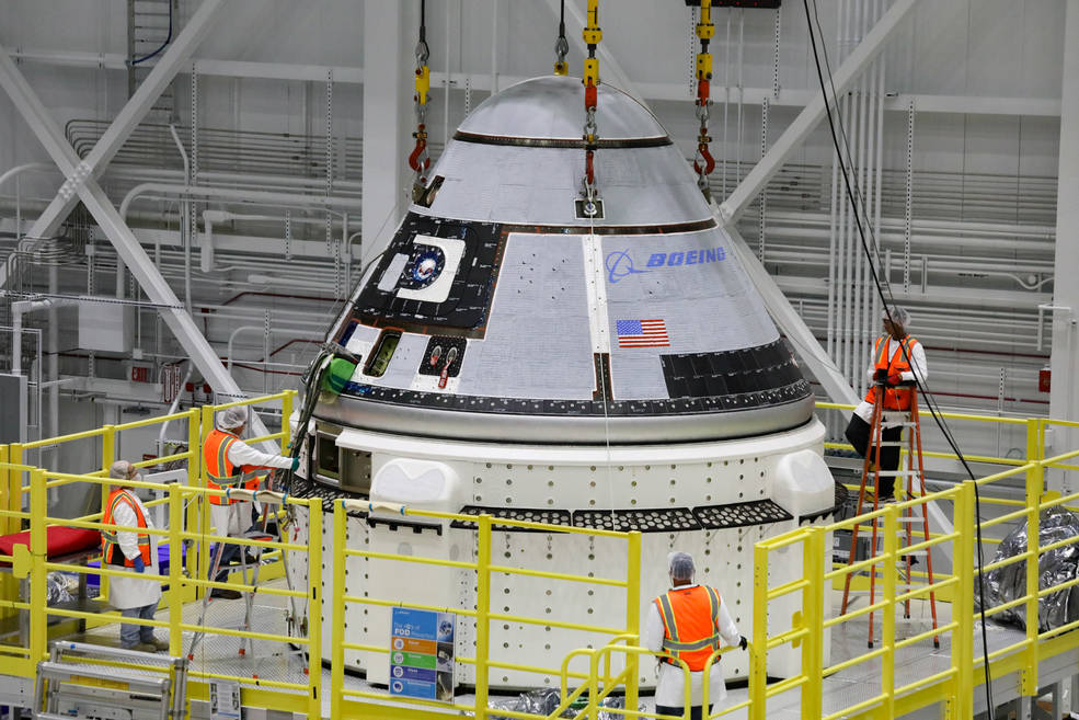 The crew module of Boeings CST-100 Starliner spacecraft is lifted onto its service module on Oct. 16.