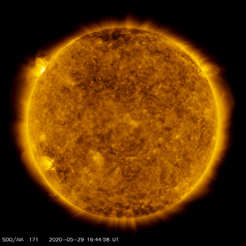 A satellite image of the Sun, colorized in gold. A bright spot of light hovers over the left horizon.
