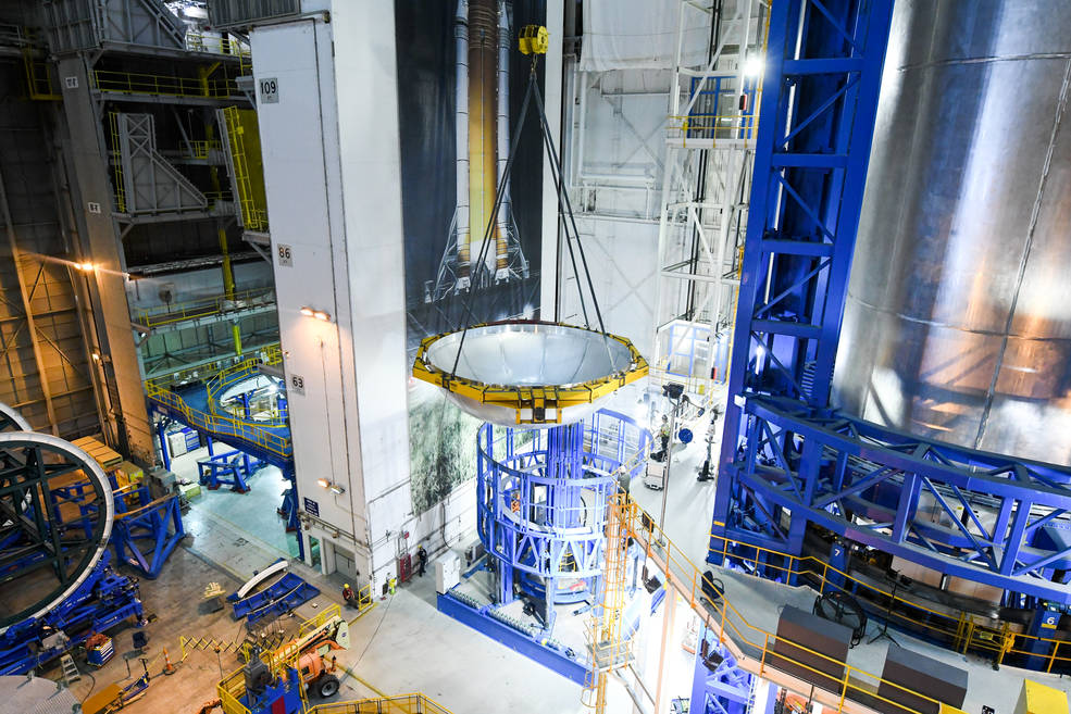 A dome is lifted into place to form the Space Launch System (SLS) liquid hydrogen tank for the first SLS flight.