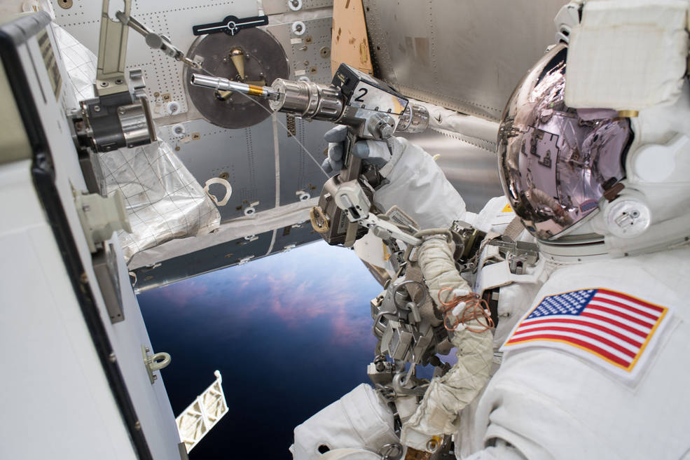 Image of an astronaut using a drill on a spacewalk