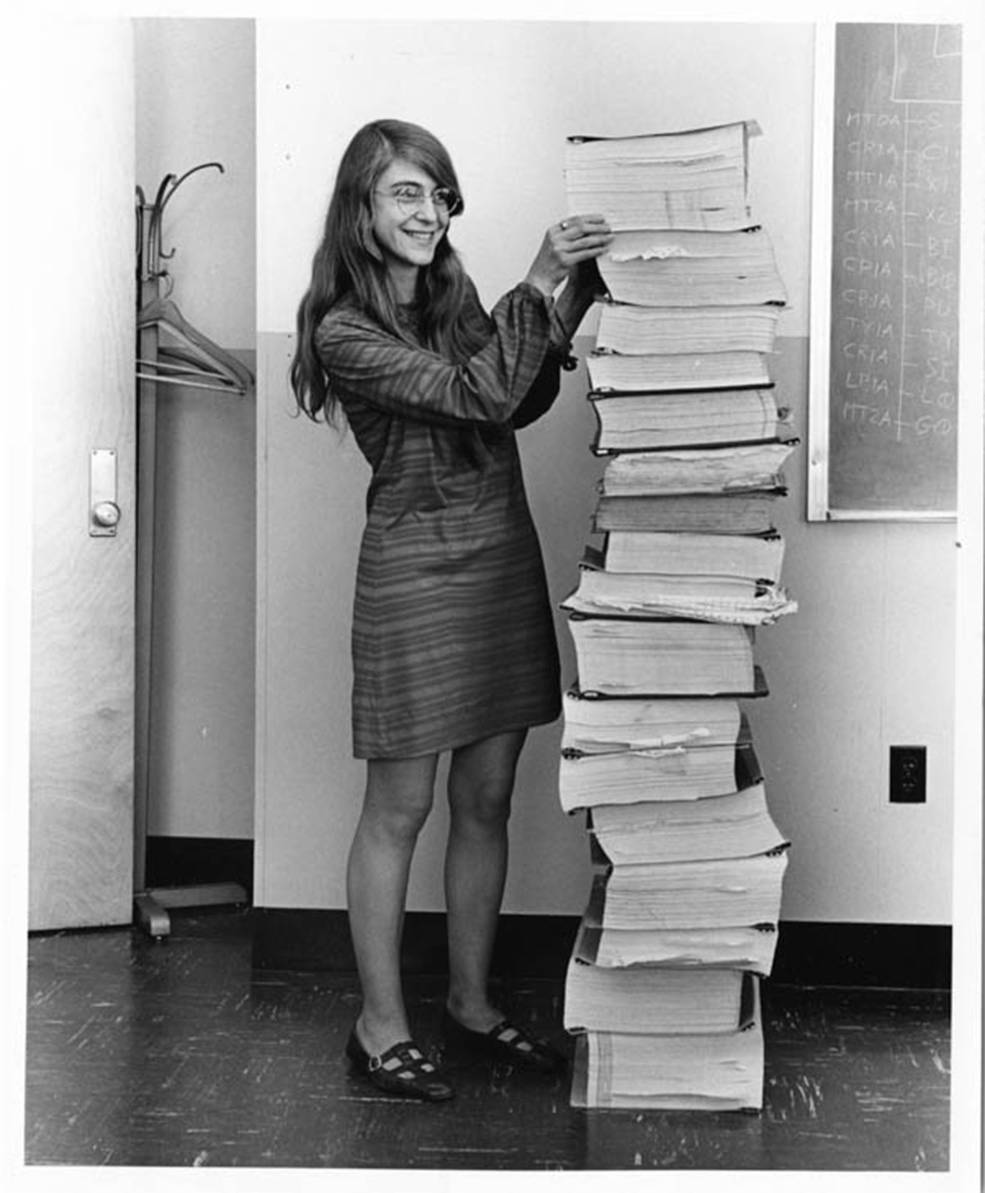 Margaret Hamilton stands next to a stack of Apollo Guidance Computer source code.