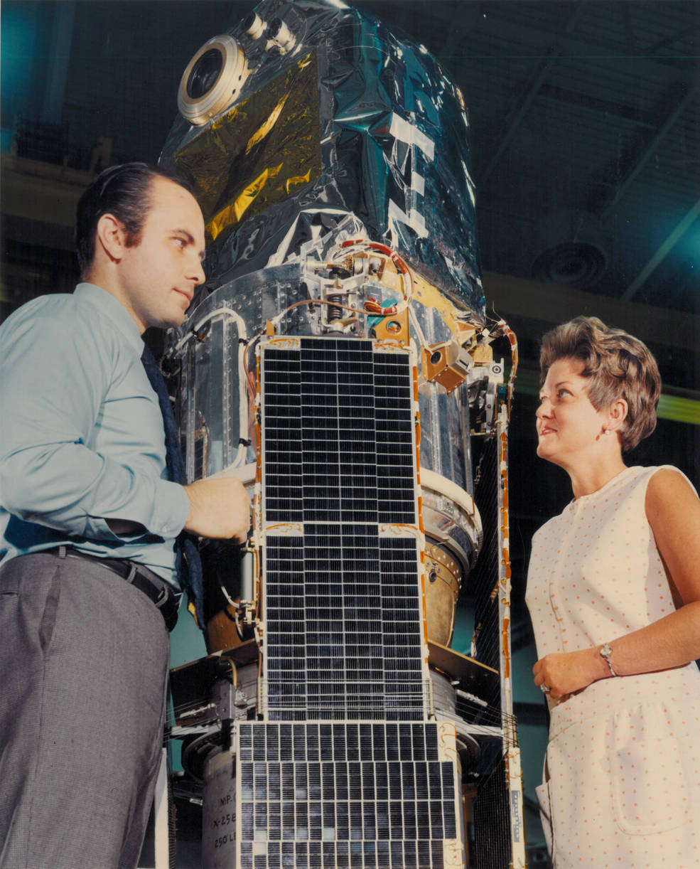 Marjorie Townsend stands in front of SAS-1 satellite and talks to man