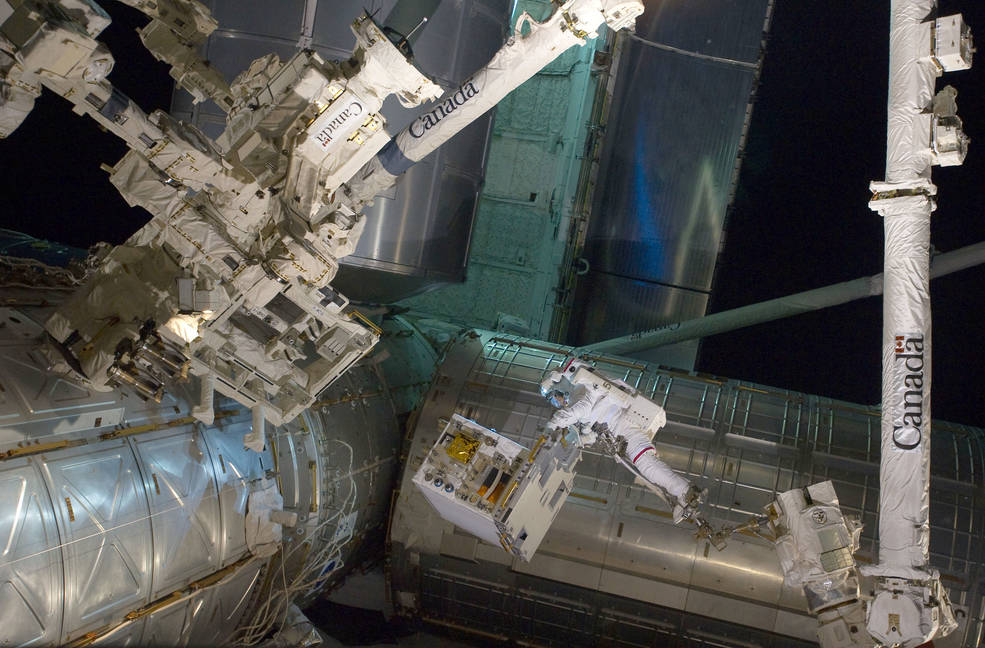 RRM module and spacewalking astronauts