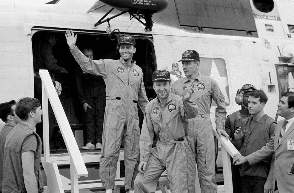 Three Apollo 13 crew members in flight suits wave while aboard USS Iwo Jima ship