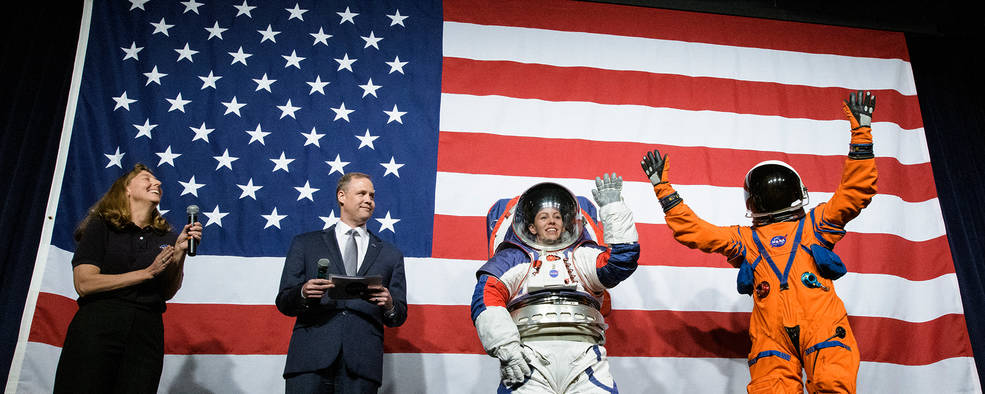 Four people in front of American flag, 2 in space suits