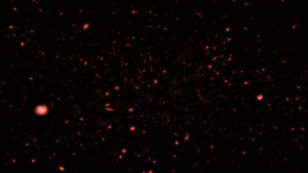 red-hued flecks of light against a black backdrop