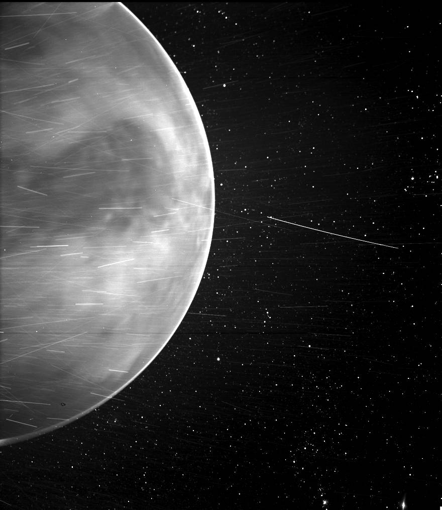 Una imagen en blanco y negro que muestra un hemisferio del planeta Venus contra un telón de fondo de estrellas, con rayas brillantes por todas partes.