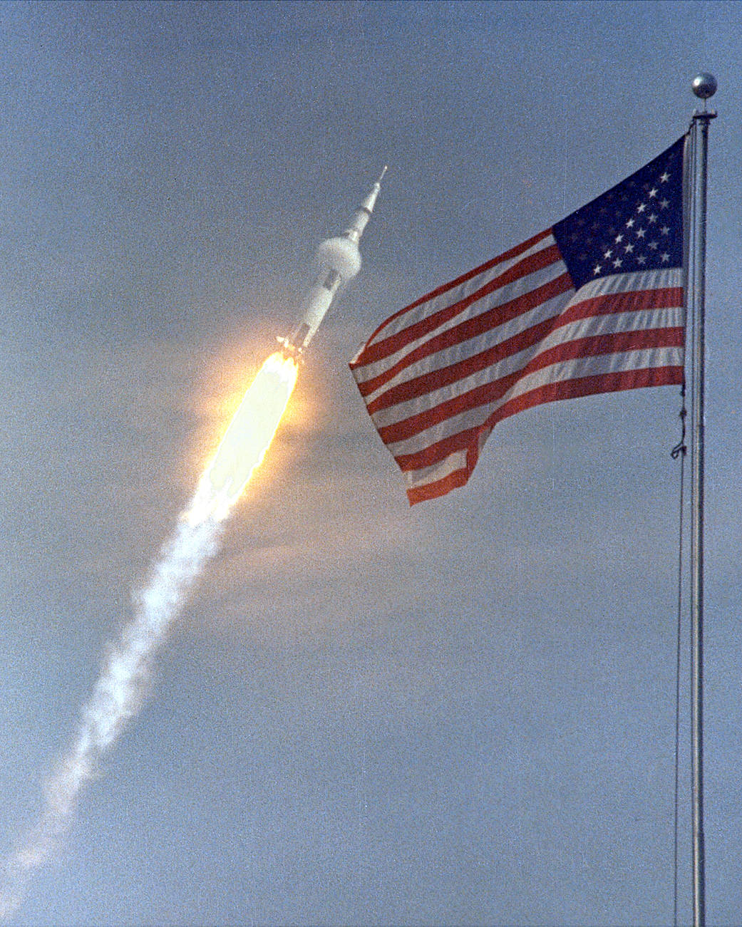 Caption from NASA: The American flag heralded the launch of Apollo 11, the first Lunar landing mission, on July 16, 1969. The massive Saturn V rocket lifted off from NASA's Kennedy Space Center with astronauts Neil A. Armstrong, Michael Collins, and Edwin