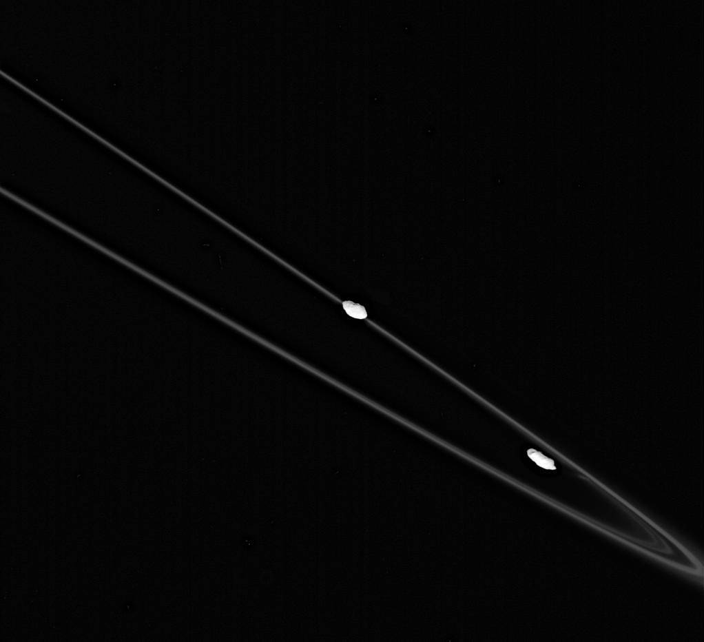 Black and white image of large, thin ring of Saturn with two small white moons circling